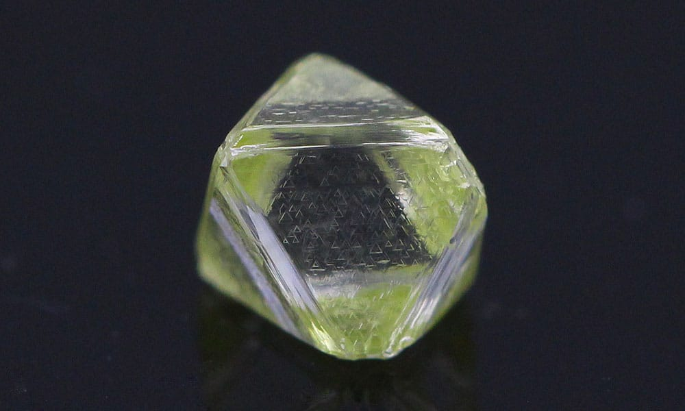 A yellow rough Diamond, the color is noticeable in the skin, while the interior of the diamond is near colorless